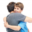Royalty-Free Stock Photo: Young boy hugging his father and smiling