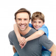 Royalty-Free Stock Photo: Caring young father giving his son piggyback ride