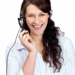 Female call centre employee speaking over the headset - Stock Photo