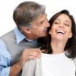 Happy mature man and his beautiful wife sharing secret - Stock Photo