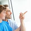 Young man showing something to his son - Stock Photo