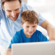 Royalty-Free Stock Photo: Happy young father and his son using laptop