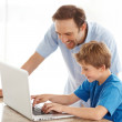 Royalty-Free Stock Photo: Happy young man and his son working on laptop