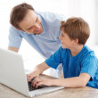 Royalty-Free Stock Photo: Happy young father and son working together on laptop