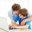 Royalty-Free Stock Photo: Happy young father hugging his son working on laptop