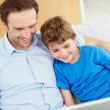 Royalty-Free Stock Photo: Happy young father and son sitting together using laptop