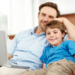Smiling young father and son relaxing on sofa with a laptop - Stockfoto