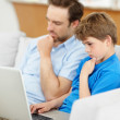 Little boy using laptop with his father reading newspaper on cou - Stock Photo