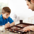 Royalty-Free Stock Photo: Father and son playing backgammon game in kitchen