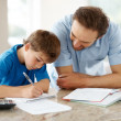 Royalty-Free Stock Photo: Happy man helping his son to do homework