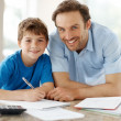 Royalty-Free Stock Photo: Smiling young father helping to his son doing homework