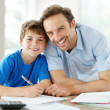 Happy young father with his son studying - Stock Photo