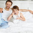 Father and son eating breakfast while watching television on bed - Stock Photo