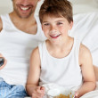 Little boy eating breakfast with his father watching television - Стоковая фотография