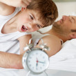 Angry little boy switching off the alarm clock in morning - Stock Photo