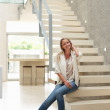 Relaxed mid adult woman sitting on stairs in a modern house - Stok fotoğraf