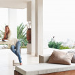 Woman sitting at a big living room with view of city - Stock Photo