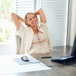 A happy casual mid adult female with computer on desk - Stockfoto