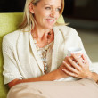 Thoughtful middle aged woman holding a cup of tea or coffee - Stockfoto