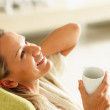 Smiling middle aged woman with a cup of tea or coffee looking up - Stockfoto