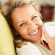 Closeup shot of a cheerful woman with a tea cup smiling - Stock Photo