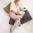 Pretty relaxed woman using laptop on floor - Stockfoto