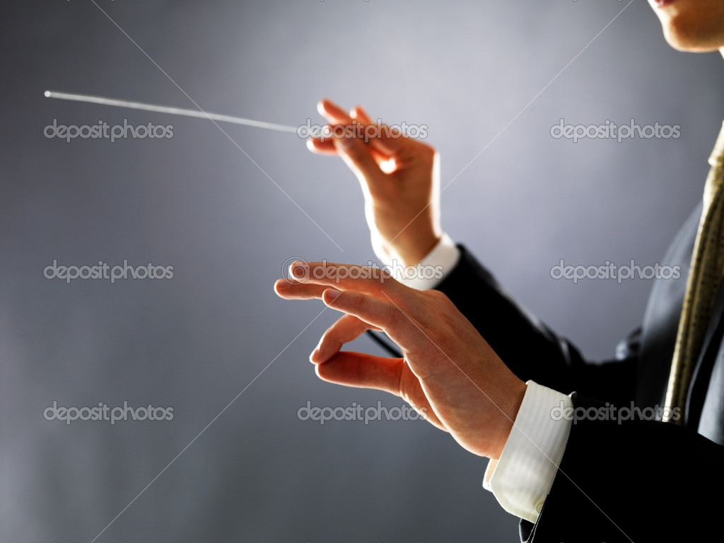 Cropped image of a male orchestra conductor directing with his baton in concert  Stock Photo #7720788
