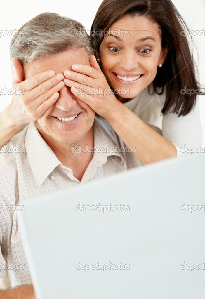 Portrait of a beautiful woman surprising a mature man working on laptop