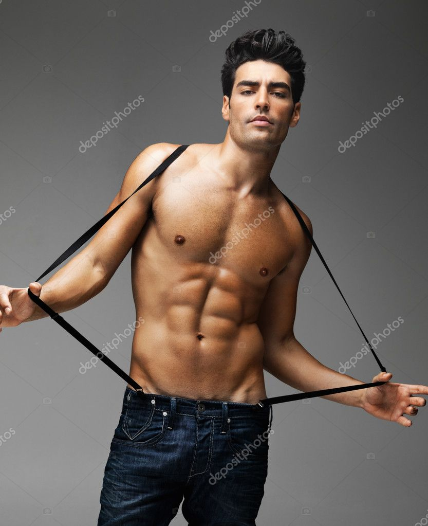 Portrait of a sexy shirtless tough guy with suspenders against gray background — Zdjęcie stockowe #7722572