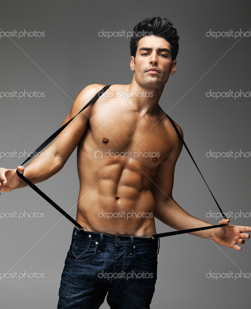 Portrait of a sexy shirtless tough guy with suspenders against gray background  Stockfoto #7722572
