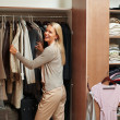 Happy mature female making choices in wardrobe - Stock Photo