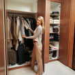 Female looking through her wardrobe and choosing clothes - Stock Photo