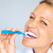 Closeup of a cheerful mature woman brushing her teeth - Stock Photo