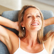 Relaxed mature woman smiling over a thought - Stok fotoğraf