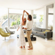Romantic mature couple dancing in a modern living room - Stok fotoğraf