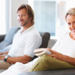 Happy mature woman reading a book with man using laptop at home - Stock Photo