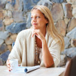 Woman contemplating over something while drinking coffee - Stock Photo