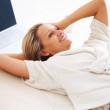 Thoughtful woman smiling in her thoughts while lying on floor - Foto Stock
