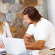 Mature couple doing home finance at dining table , using laptop - Zdjcie stockowe