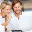 Cheerful mature couple looking at laptop screen together at home - Stock Photo