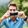 Royalty-Free Stock Photo: Handsome young guy taking photo with cellphone