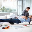 Happy young couple relaxing at home in free time - Stockfoto