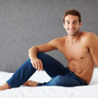 Shirtless young man sitting on the bed - Copyspace - Stock Photo