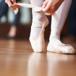 Ballerina putting her shoes on with a blurred man in background - Lizenzfreies Foto