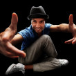 Happy young bboy pointing at you against dark background - Stock Photo