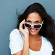 Beautiful brunette flirting looking over sunglasses - Stock Photo