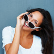 Brunette looking over sunglasses and smiling - Stock Photo