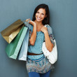 Happy brunette holding shopping bags - Stockfoto