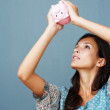 Brunette looking for money in piggy bank - Stock Photo