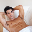 Royalty-Free Stock Photo: Young male underwear model posing on sofa